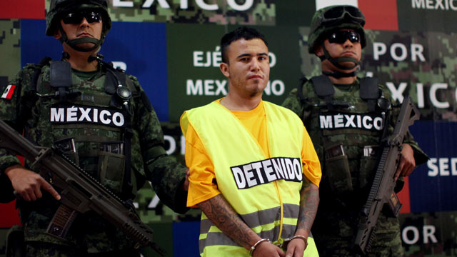 "PHOTO: Army soldiers flank Daniel Ramirez, alias ""El Loco,"" during his presentation to the media in Mexico City on May 21, 2012."