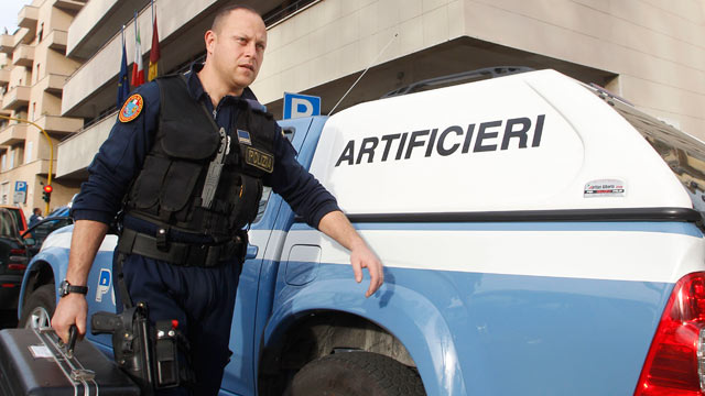 PHOTO: An Italian bomb expert police officer walks outside Equitalia tax collection agency after a letter bomb was intercepted at the offices, in Rome, Dec. 15, 2011.