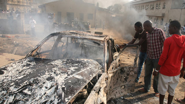 PHOTO: Men look at the wreckage of a car following a bomb blast at St Theresa Catholic Church outside the Nigerian capital Abuja, Dec. 25, 2011.