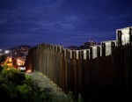 PHOTO: The US and Mexican border wall is illuminated at night, July 6, 2012, in Nogales, Arizona.