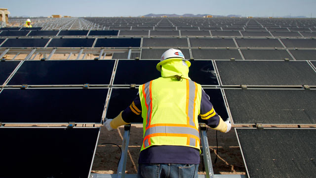 PHOTO: A worker installs First Solar Inc. photovoltaic solar panels at the Agua Caliente Solar Project in Yuma County, Arizona, U.S., Feb. 16, 2012.