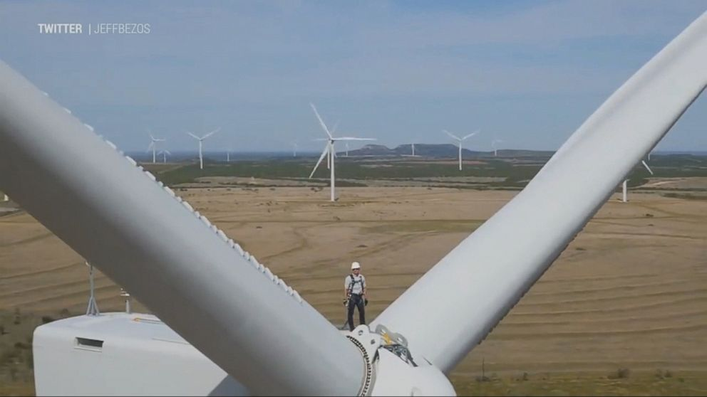 Amazon CEO smashes bottle of champagne on top of wind turbine Video ...