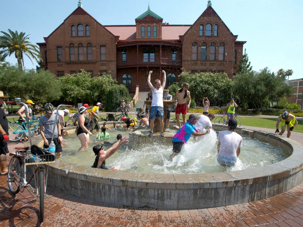 PHOTO: People cool off in the fountain in front of Old Main on Arizona State University campus in Tempe, Ariz. during the Tempe Bicycle Action Group swimsuit ride, June 29, 2013.