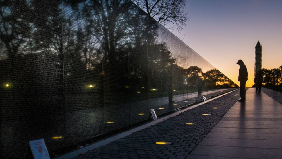 A visitor at the Vietnam Veterans Memorial in Washington passes early in the morning on Veterans Day, Nov. 11, 2013, to look at the names inscribed on the wall.