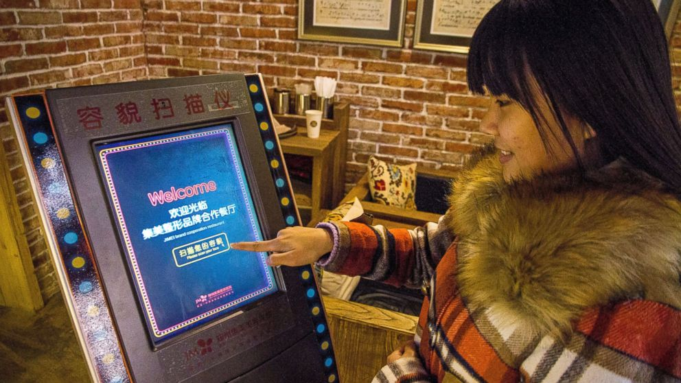 A customer uses a face-scanning machine at a restaurant offering free meals to customers who earn high marks for their looks in Zhengzhou city, China, Jan. 11, 2015.