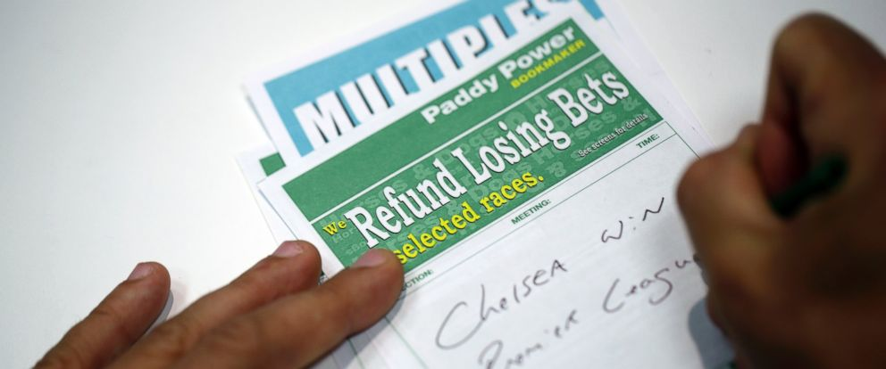 PHOTO: A photo illustration showing a client filling in a betting slips at a Paddy Power Plc bookmakers in London, U.K., Aug. 25, 2015.