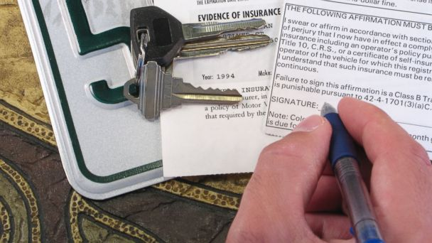 PHOTO: A man signs car insurance forms.