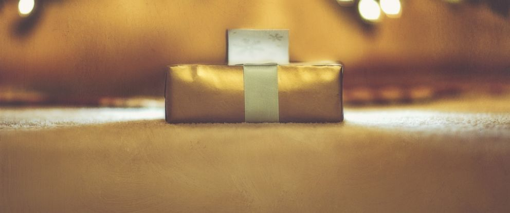 PHOTO: A wrapped Christmas present sits under a Christmas tree.