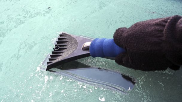 PHOTO: An ice scraper is used to remove a thick layer of ice from a car windshield.