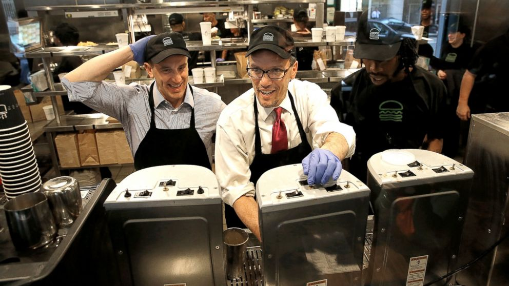 U.S. Labor Secretary Thomas Perez, center, talks with Shake Shack employee Jamelle Bland, right, while making a milkshake during a tour of the restaurant with Shake Shack CEO Randy Garutti, left, March 21, 2014, in Washington. Perez toured the restaurant to participate in a discussion on the federal minimum wage, and the Obama administration's efforts to raise the minimum wage to $10.10.
