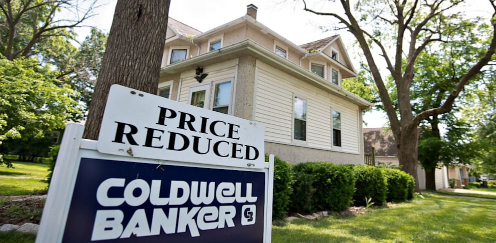 """PHOTO: A """"price reduced"""" sign stands outside a home for sale in LaSalle, Illinois, June 7, 2013."""