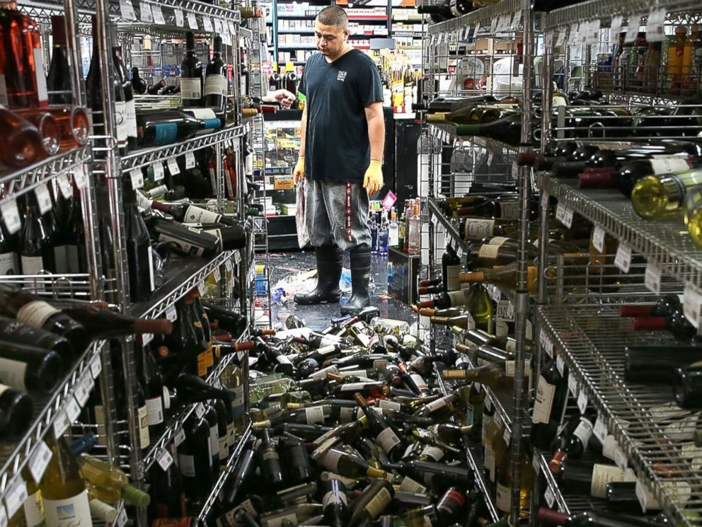 PHOTO: A worker looks at a pile of wine bottles that were thrown from the shelves at Vans Liquors following a reported 6.0 earthquake on Aug. 24, 2014 in Napa, Calif.