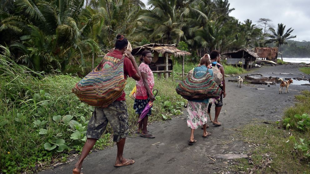 Women carry wood in the town of Kerema, Papua New Guinea, Sept. 5, 2014.