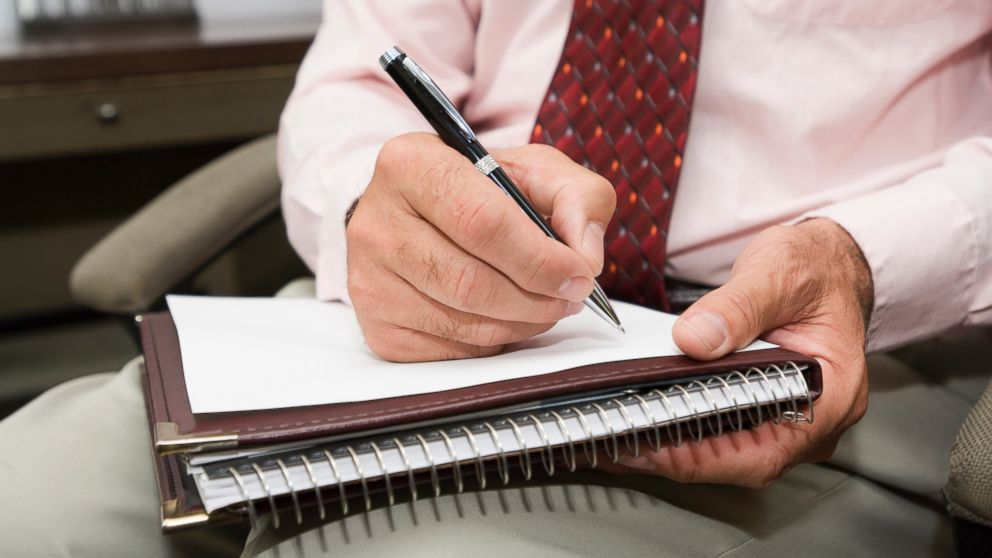 A psychologist jots down some notes with a pen while in session with a client.