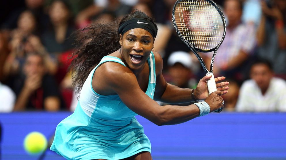 Serena Williams of the Singapore Slammers runs to play a backhand against Kirsten Flipkens of the Manila Mavericks during the Coca-Cola International Premier Tennis League at the Mall of Asia Arena, Nov. 30, 2014, in Manila, Philippines.