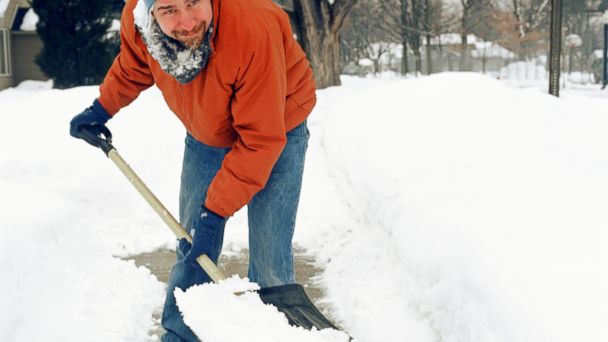 PHOTO: A man shovels snow using a shovel with a D-grip handle.
