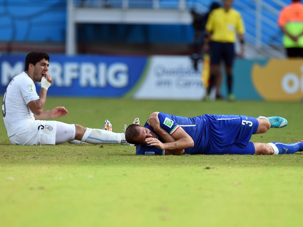 PHOTO: Uruguays forward Luis Suarez left, reacts past Italys defender Giorgio Chiellini during a Group D football match between Italy and Uruguay at the Dunas Arena in Natal during the 2014 FIFA World Cup on June 24, 2014.