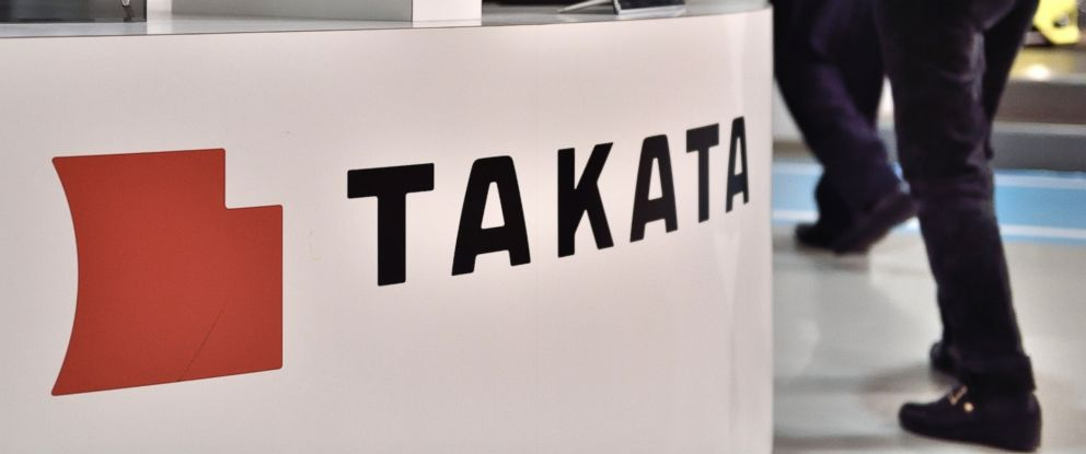 PHOTO: Visitors walk past displays of Japanese auto parts maker Takata Corp. at a car showroom in Tokyo on Nov. 11, 2014.