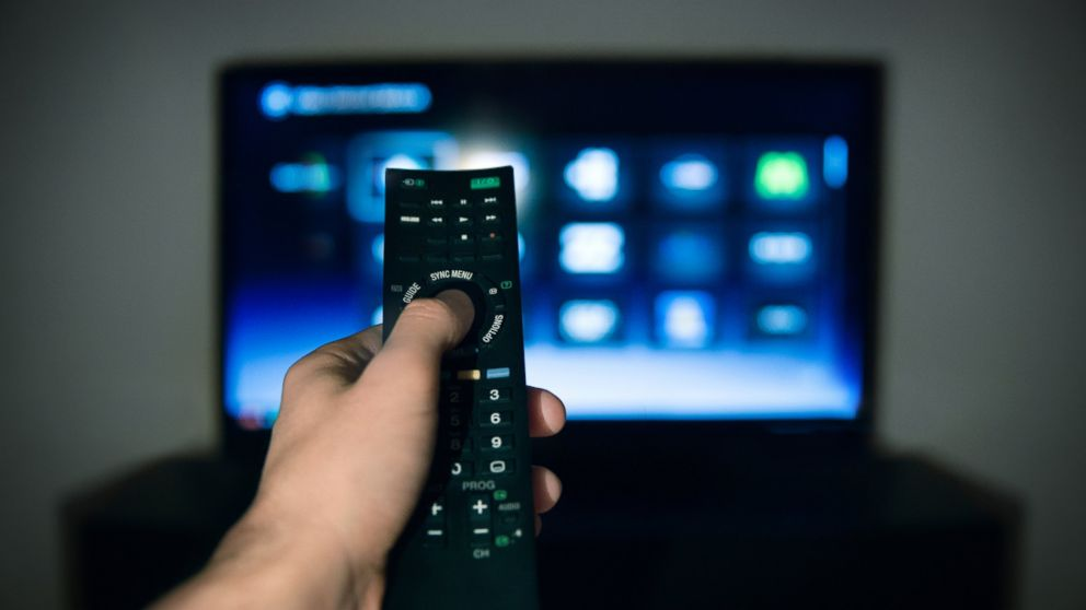 A man is pictured using a remote control for his television in this stock image.