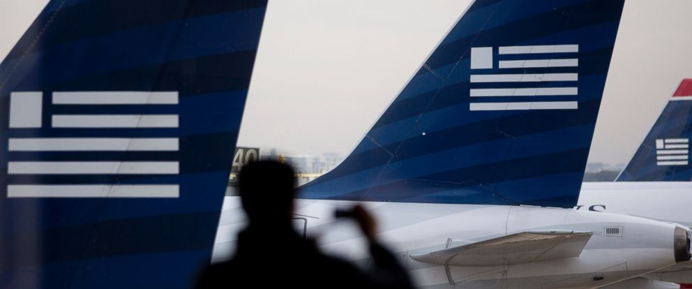 PHOTO: In this file photo, the silhouette of a traveler is seen taking a photograph of US Airways planes parked on the tarmac at Ronald Reagan National Airport in Washington, D.C. on Nov. 15, 2013.