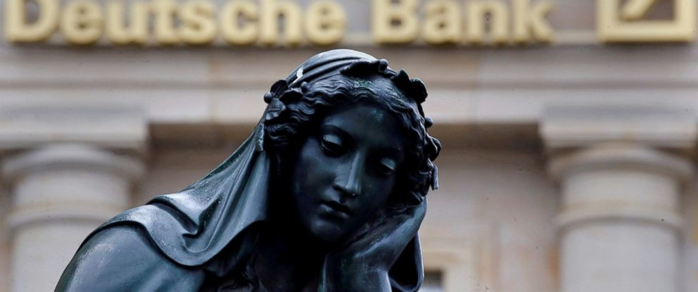 PHOTO: A statue is seen next to the logo of Germanys Deutsche Bank in Frankfurt, Germany, Jan. 26, 2016.