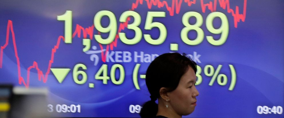 A currency trader walks by a screen showing the Korea Composite Stock Price Index (KOSPI) at the foreign exchange dealing room in Seoul, South Korea, Tuesday, Aug. 13, 2019. Asian stock markets followed Wall Street lower Tuesday amid anxiety the U.S.