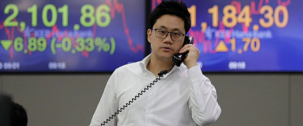 A currency trader talks on the phone near the screens showing the Korea Composite Stock Price Index (KOSPI), left, and the foreign exchange rate between U.S. dollar and South Korean won at the foreign exchange dealing room in Seoul, South Korea, Thur