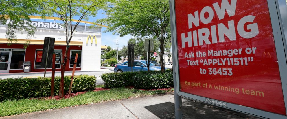 In this Monday, July 1, 2019 photo, a help wanted sign appears on a bus stop in front of a McDonalds restaurant in Miami. On Tuesday, July 9, the Labor Department reports on job openings and labor turnover for April. (AP Photo/Wilfredo Lee)