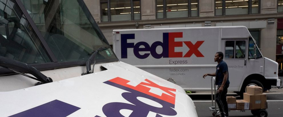 In this Tuesday, Aug. 22, 2017, photo, FedEx trucks are parked in New York. FedEx is dropping a contract for air shipment of packages for Amazon within the United States, reducing its ties with the online retail giant that is already expanding its ow