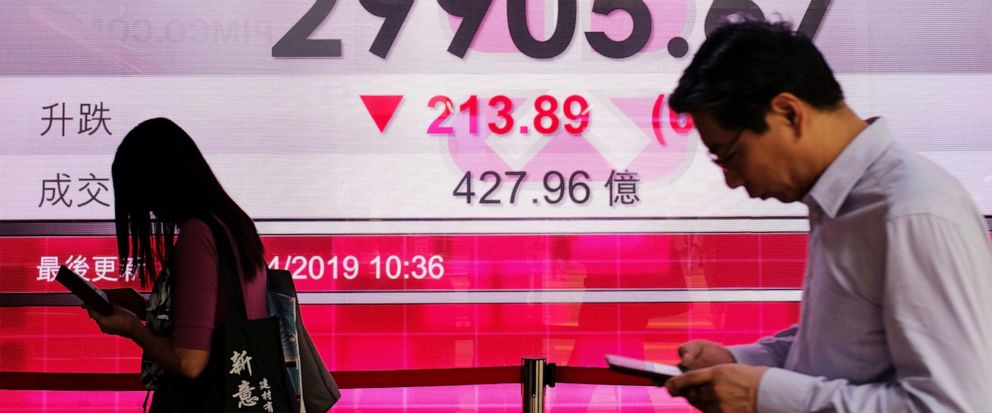 People walk past an electronic board showing Hong Kong share index outside a local bank in Hong Kong, Thursday, April 11, 2019. Asian markets retreated Thursday on news that most U.S. Federal Reserve officials believed the central bank would leave in