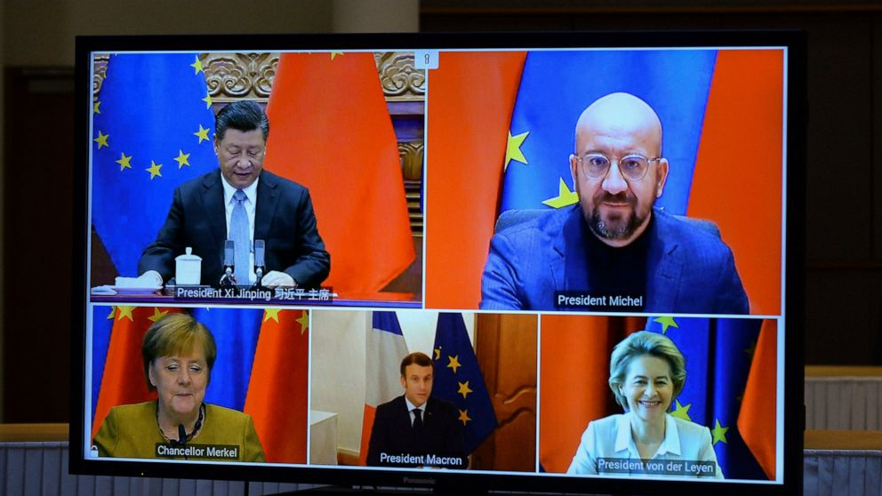 A screen displays live Chinese President Xi Jinping, top left, European Council President Charles Michel, top right, European Commission President Ursula von der Leyen, bottom right, French President Emmanuel Macron, bottom center, and German Chancel