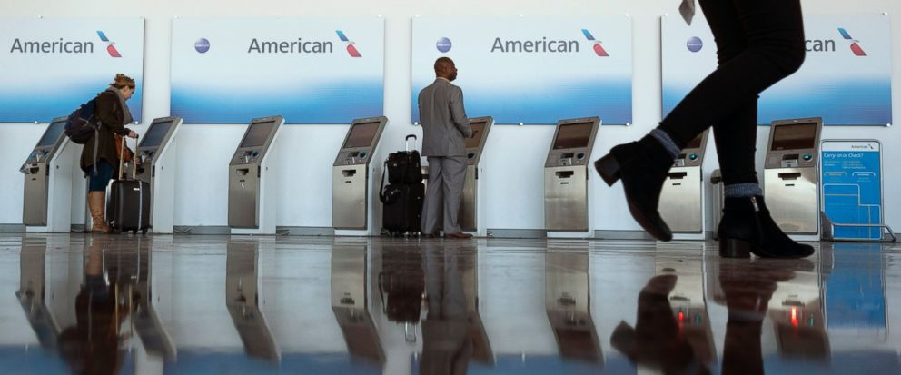 FILE- In this Nov. 21, 2018, file photo travelers checkin in at American Airlines kiosks at Washington Reagan National Airport in Arlington, Va. Airline stocks are falling as American Airlines says fourth-quarter revenue and full-year profit will be