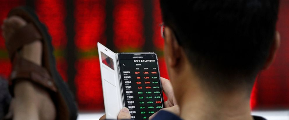 A man checks stock prices through his smartphone at a brokerage house in Beijing, Thursday, July 11, 2019. Shares rose Thursday in Asia, tracking gains on Wall Street after Federal Reserve Chairman Jerome Powell suggested the U.S. central bank is rea