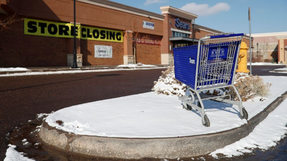 FILE- In this Tuesday, Jan. 1, 2019, file photo, an empty shopping cart sits in the snow outside a Sears store in the Streets of Southglenn mall in Littleton, Colo. Sears is getting another reprieve from liquidation after its chairman and largest shareholder revised his bid to save the iconic brand. The Hoffman Estates, Illinois-based retailer says it has accepted Eddie Lampert's bid through an affiliate of his ESL hedge fund that could keep 425 stores open and save tens of thousands of workers, according to a hearing on Tuesday, Jan. 8, 2019, at the bankruptcy court in White Plains, N.Y. (AP Photo/David Zalubowski, File)