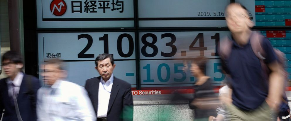 People walk past an electronic stock board showing Japans Nikkei 225 index at a securities firm in Tokyo Thursday, May 16, 2019. Asian shares were mixed Thursday as worries remained about trade tensions, tempered by media reports that President Dona