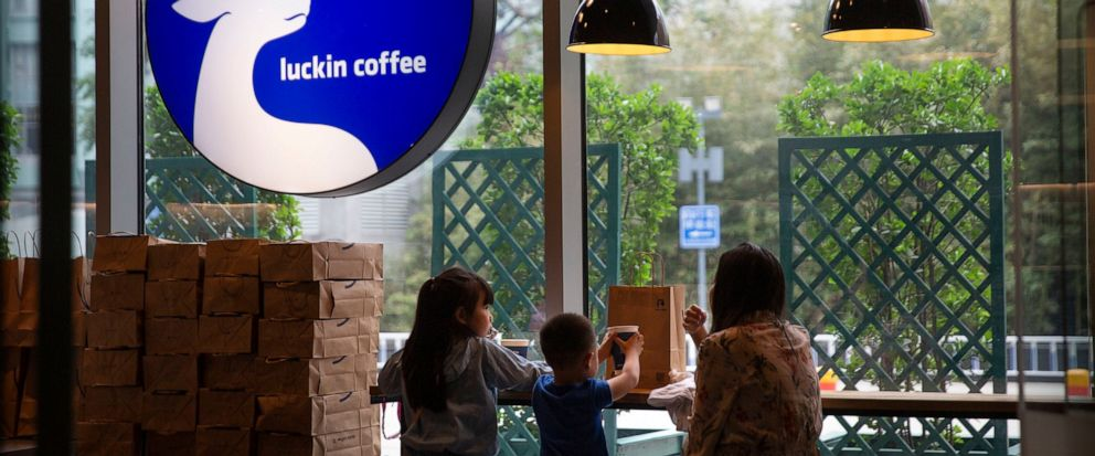Customers sit inside a Luckin Coffee shop at a shopping center in Beijing, Saturday, May 18, 2019. Shares of Luckin Coffee, a fast-growing rival to Starbucks in China, rose 20% in their U.S. stock market debut Friday. (AP Photo/Mark Schiefelbein)