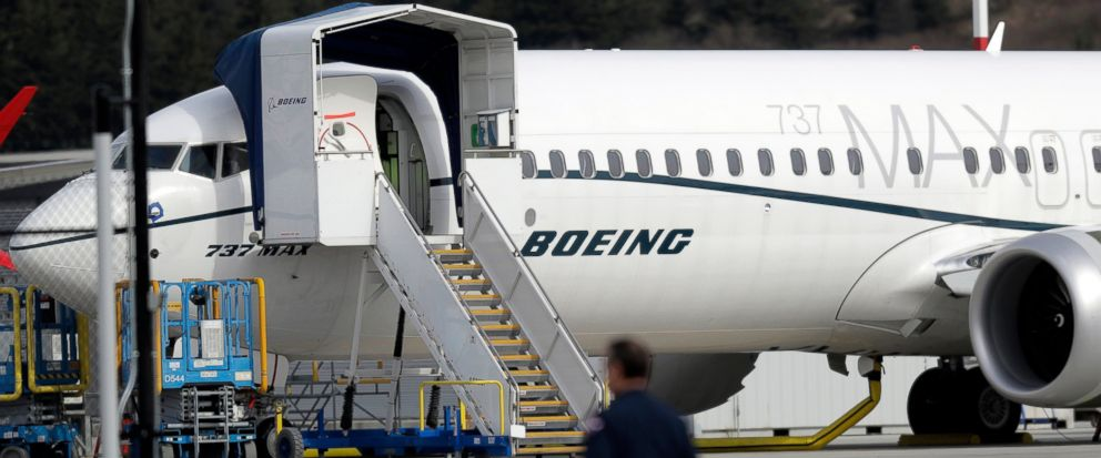 A worker walks next to a Boeing 737 MAX 8 airplane parked at Boeing Field, Thursday, March 14, 2019, in Seattle. The fatal crash Sunday of a 737 MAX 8 operated by Ethiopian Airlines was the second fatal flight for a Boeing 737 Max 8 in less than six