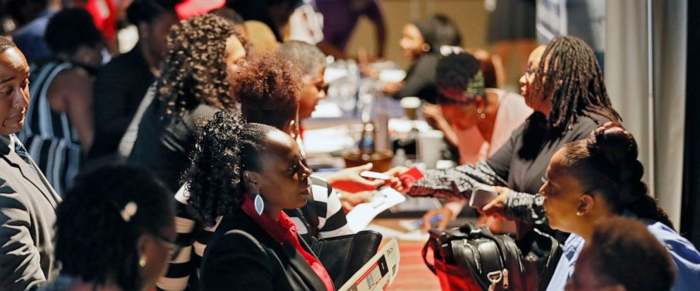 FILE - In this Aug. 14, 2019, file photo company representatives from Verizon, Goodwill, Kaiser Permanente and UPS, right, talk with potential applicants during a job and resource fair in Atlanta. On Friday, Sept. 6, the U.S. government issues the Au