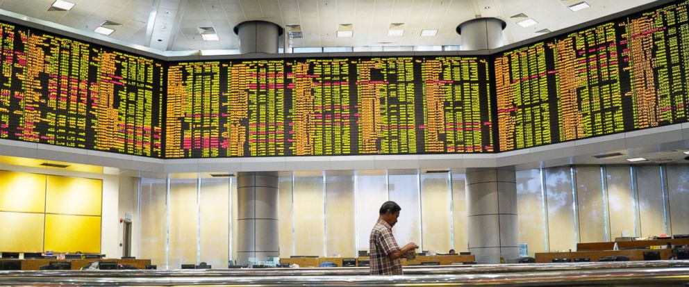 In this Dec. 26, 2018, photo, an investor walks in front of private stock trading boards at a private stock market gallery in Kuala Lumpur, Malaysia. (AP Photo/Yam G-Jun)