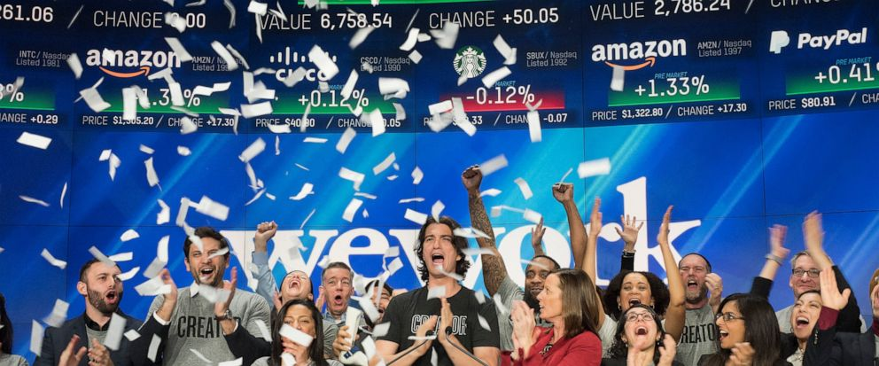 FILE - In this Jan. 16, 2018 file photo, Adam Neumann, center, co-founder and CEO of WeWork, attends the opening bell ceremony at Nasdaq in New York. Office space-sharing company WeWork is getting ready to go public, adding to a growing list of tech