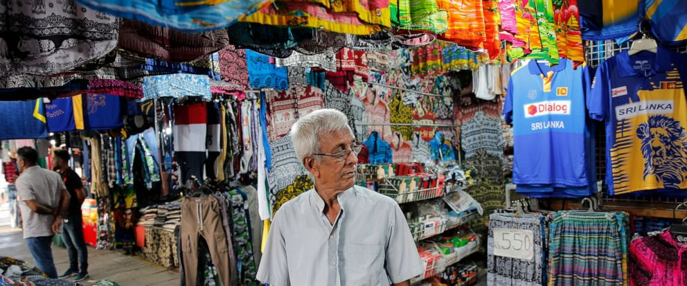 In this July 24, 2019, photo, Sri Lankan trader Ranepura Hewage Jayasena, 76, waits for customers at shop selling mementos in Colombo, Sri Lanka. Shocks from deadly suicide bombings on Easter Day in Sri Lanka are still reverberating throughout its ec