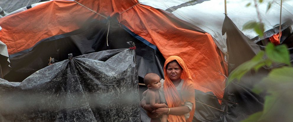 FILE - In this June 29, 2018, file photo, Rohingya refugees look out from their camp near a fence during a government-organized media tour to a no-mans land between Myanmar and Bangladesh, near Taungpyolatyar village, Maung Daw, northern Rakhine Sta