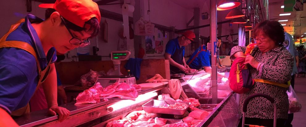 In this Wednesday, Sept. 11, 2019, photo, a clerk stacks cuts of pork at a meat market in Beijing. Chinese families are having to rethink menu options as pork prices soar despite government efforts to rebuild herds decimated by African swine fever an