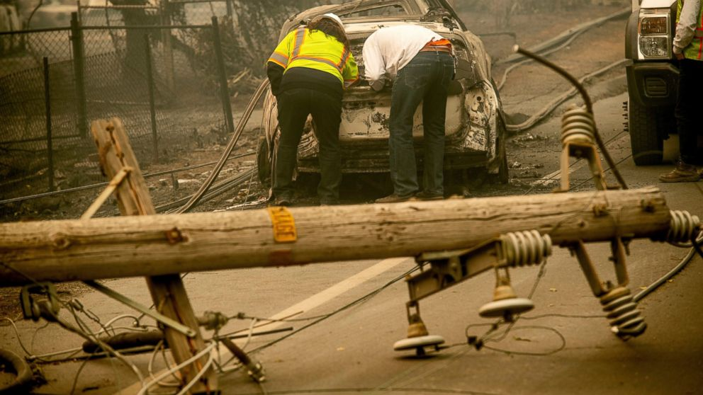 "FILE - In this Nov. 10, 2018 file photo, with a downed power utility pole in the foreground, Eric England, right, searches through a friend's vehicle after the wildfire burned through Paradise, Calif. California's largest utility company is getting battered in midday trading on a report that it's considering bankruptcy protection in the face of potentially crippling liability damages from a spate of recent wildfires. No cause has been determined for the source of California's ""Camp Fire,"" but PG&E reported an outage around the time and place the fire was ignited. Another transmission line also malfunctioned a short time later, possibly sparking a second fire. (AP Photo/Noah Berger, File)"