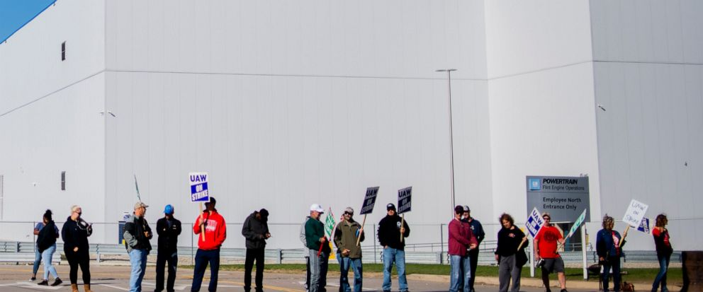 General Motors Flint Assembly Plant employees line the street with picket signs during the nationwide UAW strike against General Motors on Monday, Oct. 7, 2019, in Flint, Mich. (Jake May/The Flint Journal via AP)