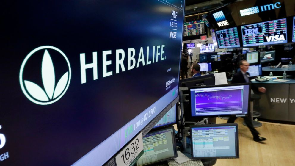 FILE - In this May 6, 2016 file photo, the Herbalife logo appears above the post where it trades on the floor of the New York Stock Exchange. Herbalife CEO Richard Goudis has resigned after the company became aware of comments he made before taking its top post that are inconsistent with its standards and don't reflect its culture. Herbalife said the comments made are also contrary to its expense-related policies and business practices and are not related to its financial reporting. Goudis will be replaced on an interim basis by former CEO Michael Johnson. (AP Photo/Richard Drew, File)