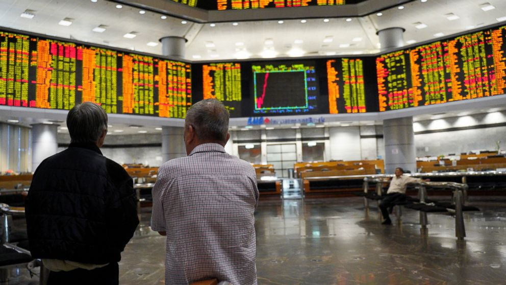 Visitors stand in front of private stock trading boards at a private stock market gallery in Kuala Lumpur, Malaysia, Friday, March 15, 2019. Shares were higher Friday in Asia after a day of lackluster trading on Wall Street. (AP Photo/Yam G-Jun)