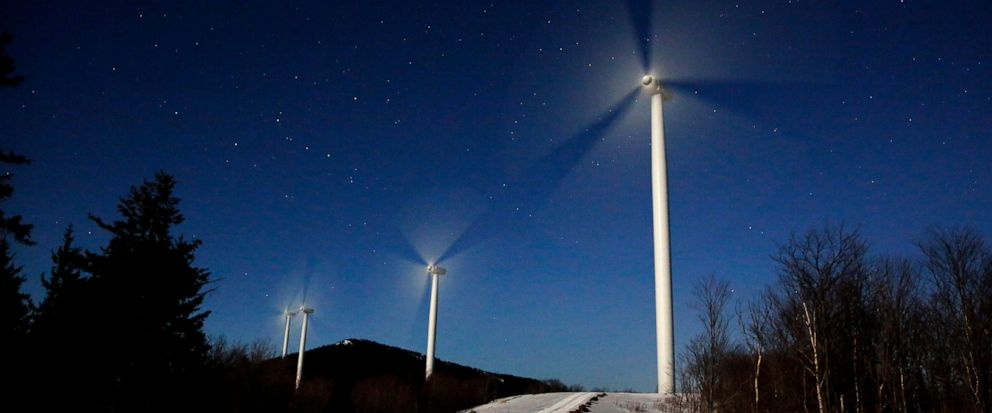 FILE- In this March 20, 2019, file photo the blades of wind turbines spin under the light of a full moon at the Saddleback Ridge Wind Project in Carthage, Maine. On Thursday, April 11, the Labor Department reports on U.S. producer price inflation in