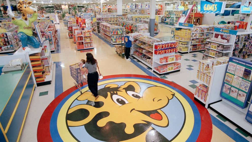 FILE- In this July 30, 1996, file photo, a woman pushes a shopping cart over a graphic of Toys R Us mascot Geoffrey the giraffe at the Toys R Us store in Raritan, N.J. Richard Barry, a former Toys R Us executive and now CEO of the new company called Tru Kids Inc., is exploring freestanding stores, shops within existing stores as well as e-commerce. Tru Kids, owned by former investors of Toys R Us, will manage the Toys R Us, Babies R Us and Geoffrey brands.s. (AP Photo/Daniel Hulshizer, File)