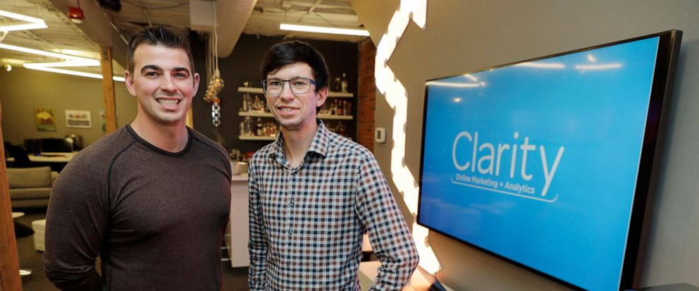 In this Tuesday, Sept. 10, 2019, photo Shane Griffiths, right, and Trenton Erker, left, co-owners of the digital marketing company Clarity Online, pose for a photo in Seattle. Griffiths and Erker use technology for tasks like billing, scheduling appo